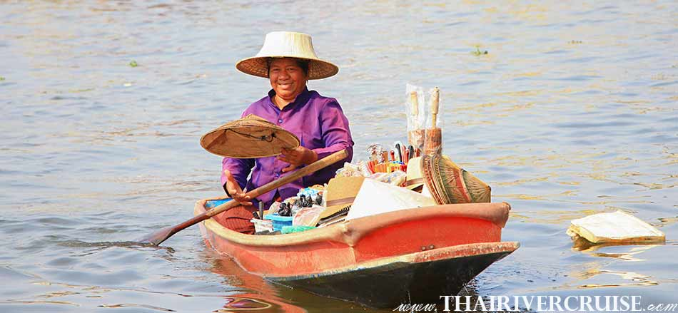 The woman wearing a traditional Thai straw hat and a big smile is one of several boat merchants in Bangkok Noi Canal, Rice Barge Canal Tour Bangkok